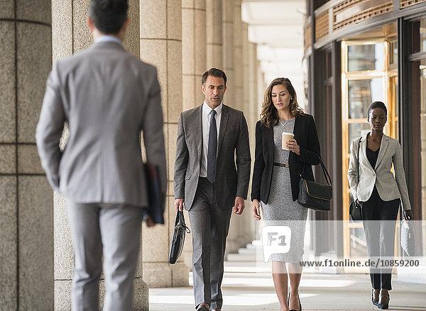 Geschäftsleute  die im Kloster spazieren gehen.
