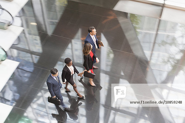 Geschäftsleute  die in der modernen Bürolobby spazieren gehen.
