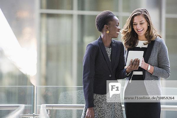 Lächelnde Geschäftsfrauen mit digitalem Tablett
