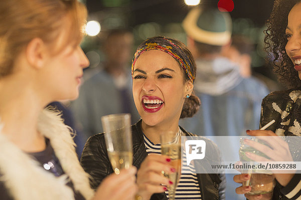 Enthusiastic young women drinking champagne and laughing at party