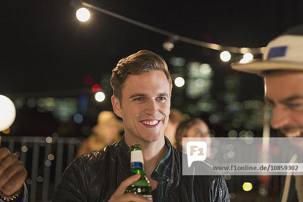 Lächelnder junger Mann trinkt Bier auf der Dachparty
