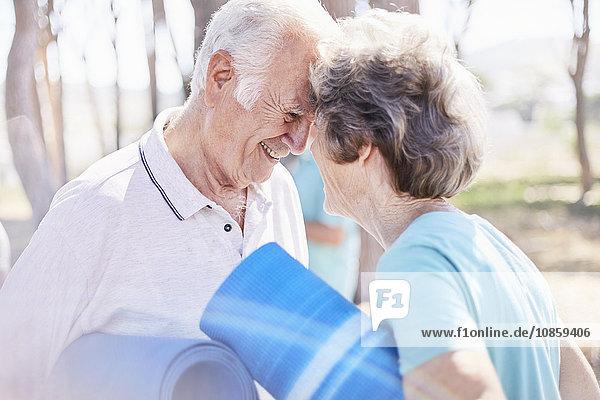 Liebevolles Seniorenpaar mit Yogamatten im Park