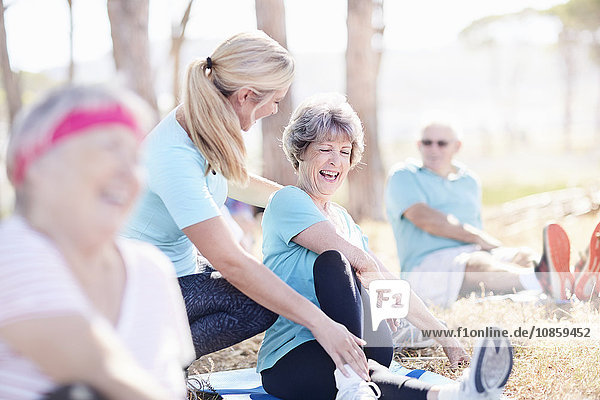 Yogalehrerin führt Seniorin im sonnigen Park