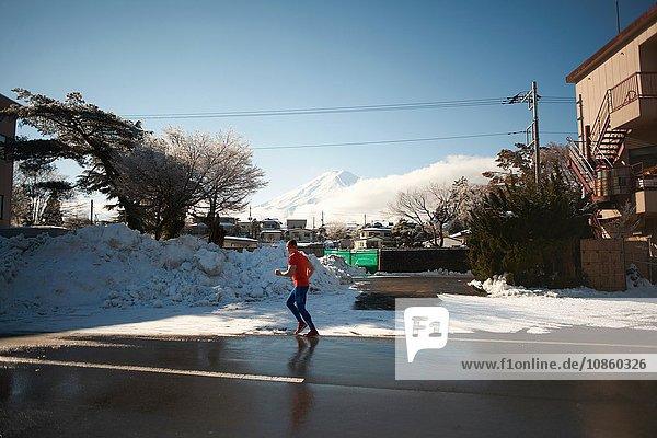 Erwachsener Mann läuft im Winter auf der Straße  Kawaguchiko-See  Berg Fuji  Japan