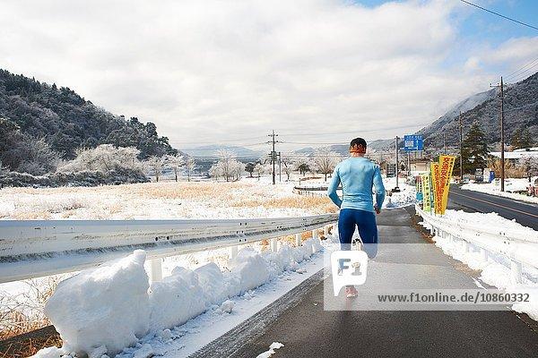 Rückansicht eines reifen männlichen Läufers  der im Winter auf der Straße läuft  Kawaguchiko-See  Berg Fuji  Japan