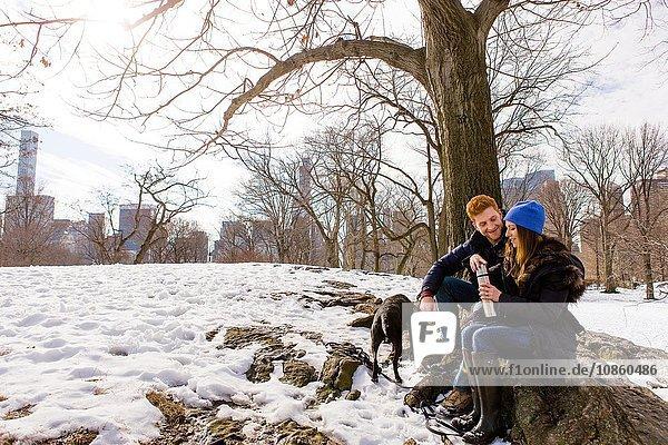 Junges Paar sitzt mit Hund und Trinkflasche im verschneiten Central Park  New York  USA