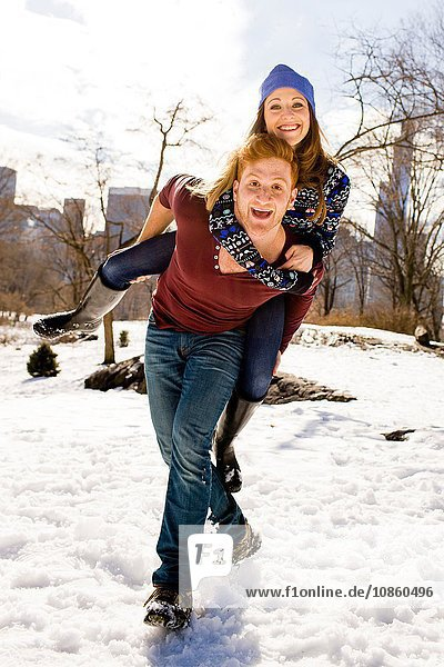 Young man giving girlfriend a piggy back in snowy Central Park  New York  USA