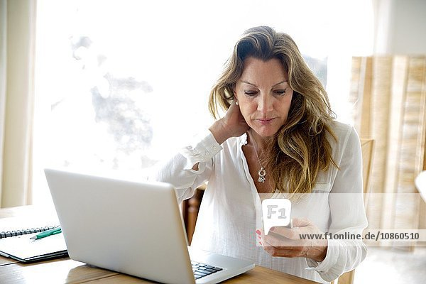 Mature woman using laptop whilst reading smartphone text at home