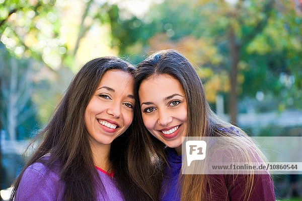 Twin sisters smiling in park
