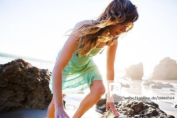 Junge Frau klettert am Strand auf Felsen