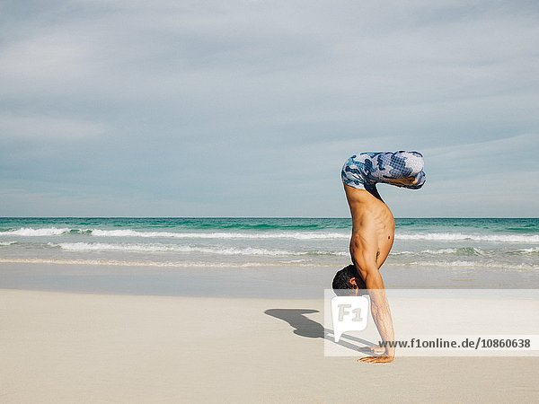 Mature man doing handstand on beach  South Pointe Park  South Beach  Miami  Florida  USA