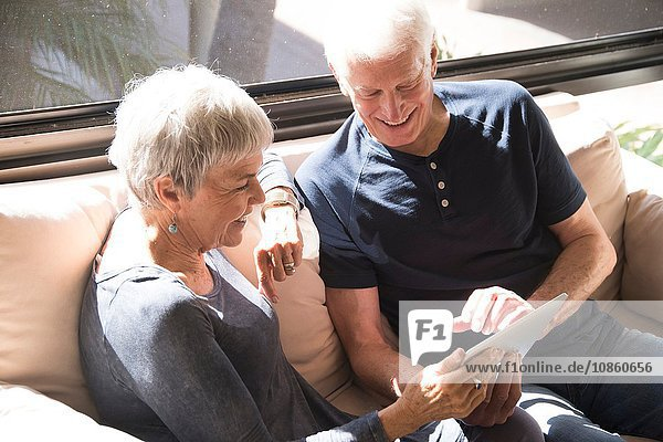 Senior couple  relaxing on sofa  looking at digital tablet