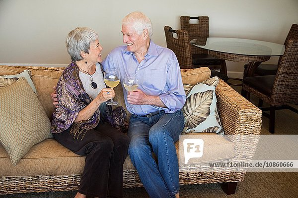 Senior couple relaxing on sofa  holding glass of wine  smiling