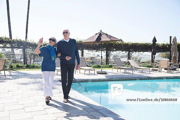 Älteres Ehepaar geht neben dem Schwimmbad