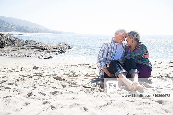 Senior couple sitting on beach  hugging  face to face  smiling