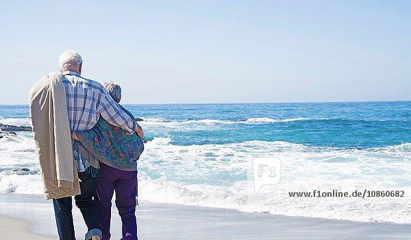 Älteres Paar am Strand stehend  Blick aufs Meer  Rückansicht