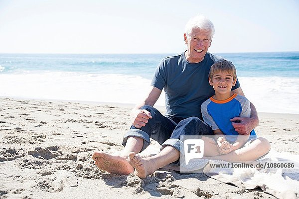 Portrait of grandfather and grandson  sitting on beach  smiling