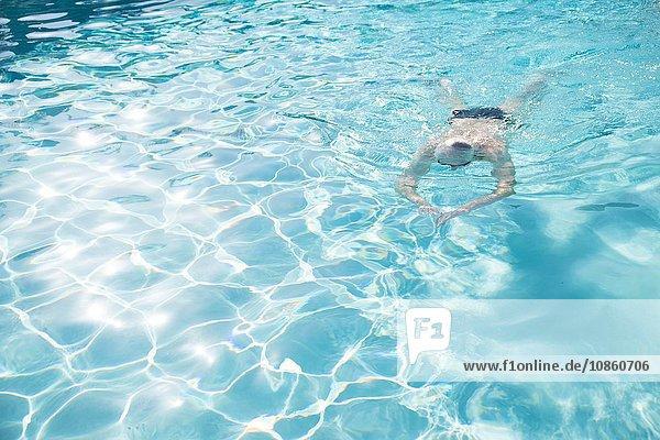 Senior man swimming in outdoor swimming pool