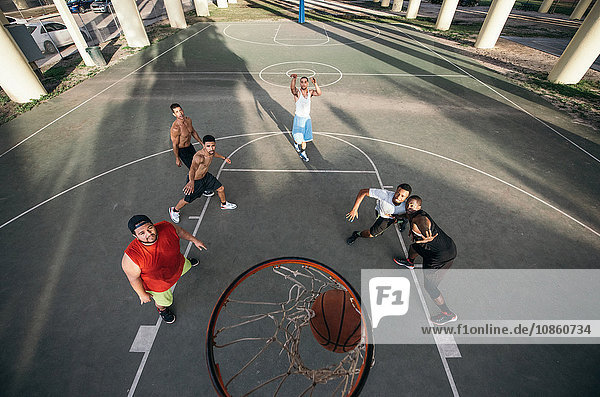 High angle view of men on basketball court watching basketball going through basketball hoop
