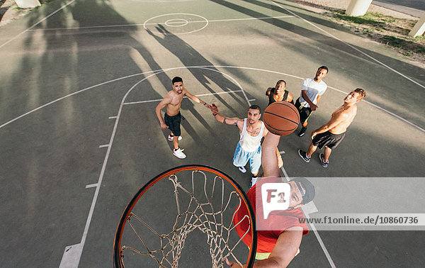 High angle view of young man on basketball court doing slam dunk