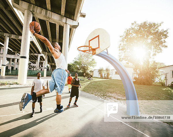 Side view of young man on basketball court holding basketball jumping for hoop