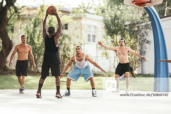 Men on basketball court playing basketball  defending hoop