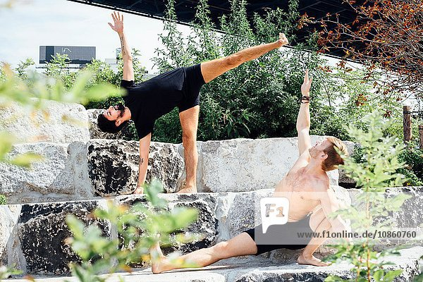 Two men practicing yoga positions together on park step