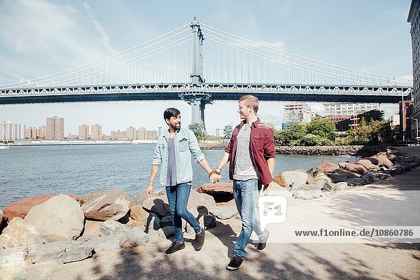 Male couple strolling on riverside by Manhattan Bridge  New York  USA