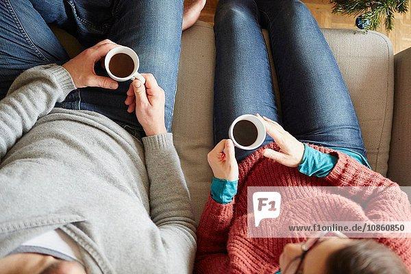Draufsicht auf ein Paar  das auf einem Sofa sitzt und eine Kaffeetasse hält