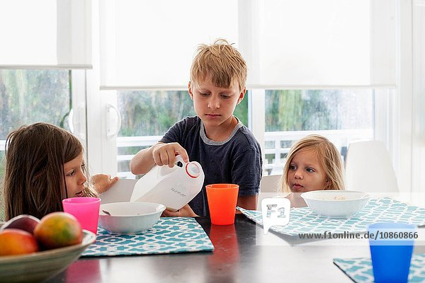 Big brother pouring milk into sisters plastic cup