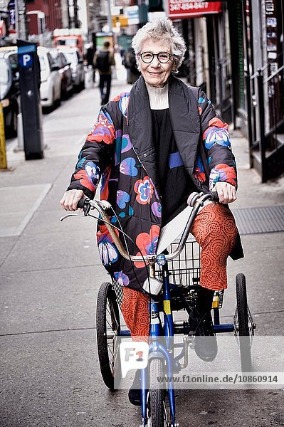 Portrait of senior woman riding tricycle