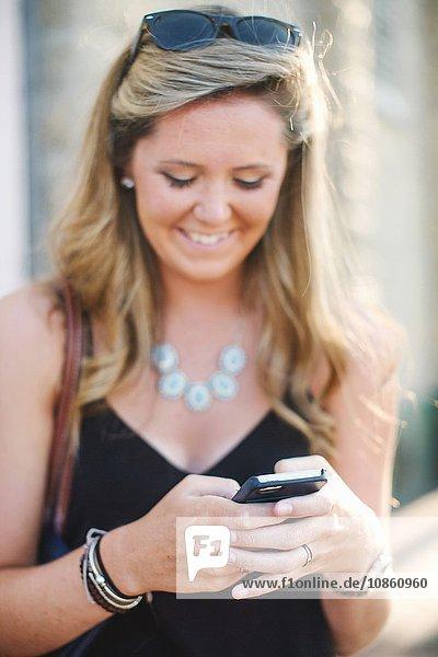 Frau schreibt auf Smartphone und schaut lächelnd nach unten