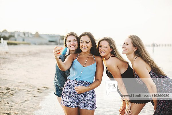 Woman on beach using smartphone to take selfie smiling