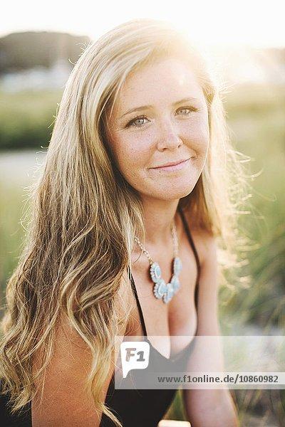 Porträt einer langhaarigen blonden Frau  die lächelnd in die Kamera schaut