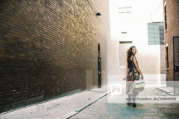 Rückansicht einer Frau in einer Gasse in voller Länge  die lächelnd über die Schulter in die Kamera schaut  Boston  Massachusetts  USA