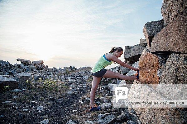 Seitenansicht des angehobenen Beins einer Frau  die sich gegen einen Felsen streckt