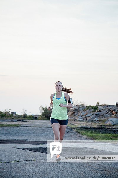 Full length front view of woman wearing activity tracker jogging