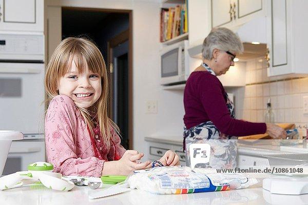 Porträt eines süßen Mädchens  das mit seiner Großmutter kocht