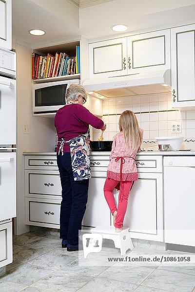 Rückansicht eines Mädchens und einer Großmutter  die den Kochtopf am Küchenherd umrühren