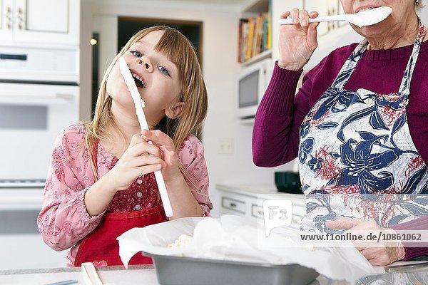 Mädchen und Großmutter lecken Kuchenmischung von Spachteln an der Küchentheke Mädchen und Großmutter lecken Kuchenmischung von Spachteln an der Küchentheke