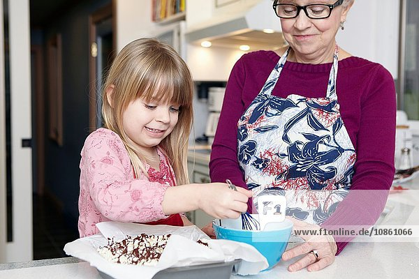 Girl whisking cake at kitchen counter with grandmother