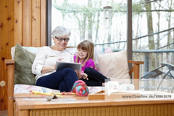 Senior woman and granddaughter using digital tablet on living room sofa
