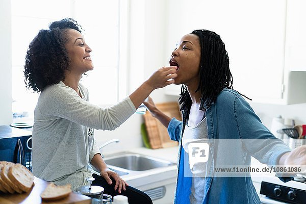Lesbian couple fooling around in kitchen
