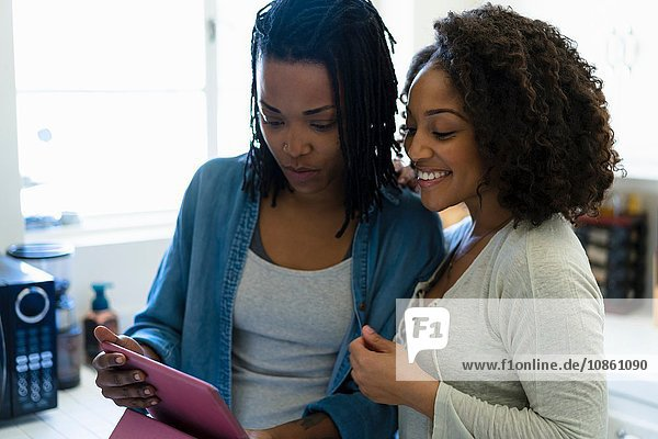 Lesbian couple in kitchen  looking at digital tablet