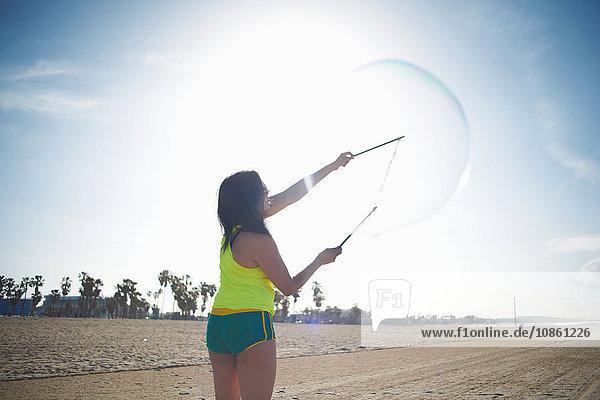 Rückansicht einer Frau am Strand  die Arme mit dem Blasenzauberstab zum Blasenmachen erhoben