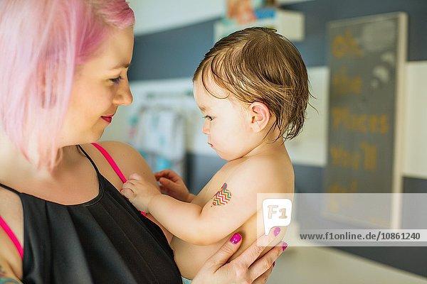 Porträt einer jungen Frau mit rosa Haaren und einem kleinen Sohn