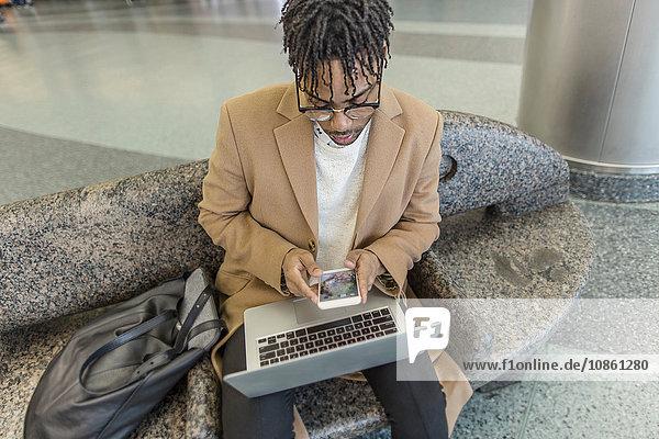 Junger Geschäftsmann sitzt im Bahnhof und benutzt Smartphone und Laptop
