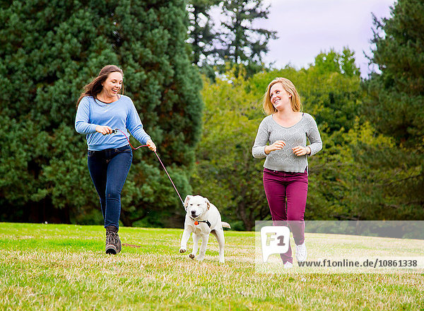 Two young women running with dog in park
