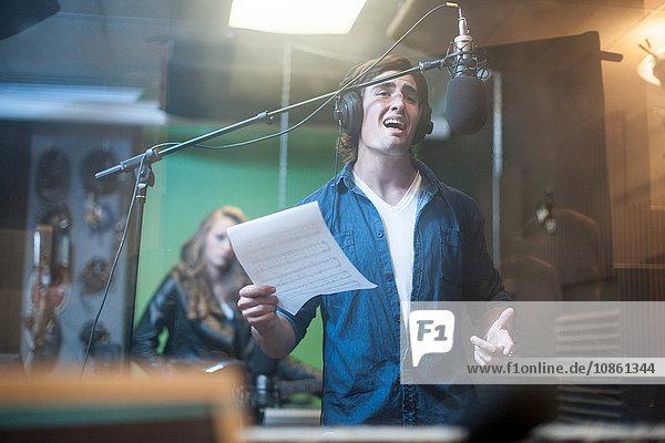 Männlicher Musiker im Aufnahmestudio  singt ins Mikrofon