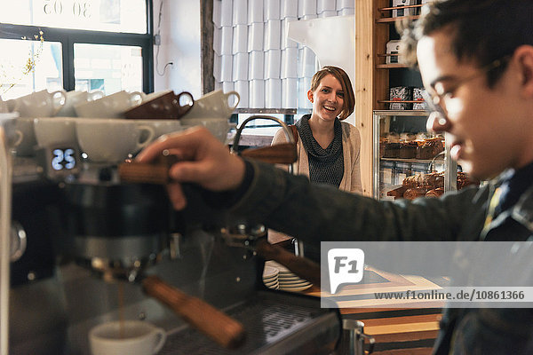 Kellner gießt Kaffee aus der Kaffeemaschine im Café